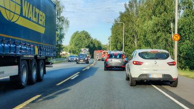 Flera bilar passerar en brandbil som står snett över vägen.