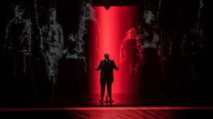 UMK-finalisti Aksel Kankaanranta seisoo laulamassa keskellä lavaa punaisessa valossa, taustalla piirrettyjä ihmishahmoja.