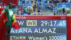 Almaz Ayana bredvid en skylt med världsrekordtiden.