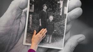 käsi vanhan valokuvan päällä