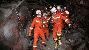 Räddningspersonal i orange overaller och hjälmar bär en person på bår.