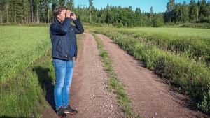 Thomas Nyström spejar ut mot åkern med en kikare