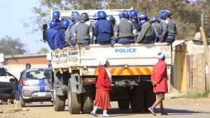 Poliser sitter på ett lastbilsflak, i förgrunden två människor.
