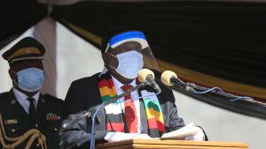 En man med mask och visir håller tal.