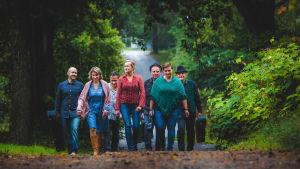 Bandet Cold Case, bestående av sju personer, går på en lummig skogsväg. de bär fodral med gitarrer.
