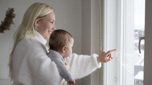 En kvinna med ett barn i famnen. Hon ler. De tittar ut genom ett fönster.