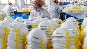 Munskydd på rad och fabriksanställda som konrollerar munskydd i Kina.