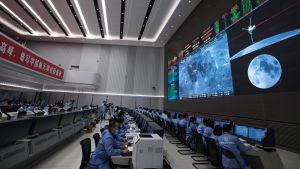 En bild tagen i kontrollrummet i Peking där många frskare sitter vid datorer och ser på en stor skärm med en bild på månen och bilder från Chang'e 5.