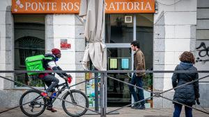 Ett cykelbud väntar på att leverera mat i Milano mitt under coornaepidemin.