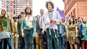 THE TRIAL OF THE CHICAGO 7, foreground from left: Caitlin Fitzgerald as Daphne O'Connor, Alex Sharp as Rennie Davis, Jeremy Strong as Jerry Rubin, John Carroll Lynch as David Dellinger, Sacha Baron Cohen as Abbie Hoffman, 2020.