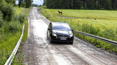 Auto ajaa kuoppaista soratietä.