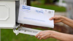 En person håller i ett kuvert med valsedlar. Hen lägger det i en postlåda.