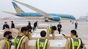 """Likkistor staplade bredvid ett turkosfärgat flygplan med beteckningen """"Vietnam Airlines"""""""