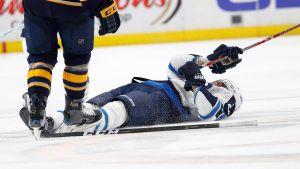 Patrik Laine ligger på isen efter hård tackling.