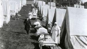 Kentällä on rivi telttoja ja telttojen edessä kenttävuoteilla makaa sairaita. Heidän vieressään seisoo sairaanhoitajia. Tummapukuinen mies kulkee telttojen välissä kulkevalla polulla.