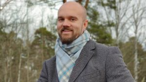 En skäggig man med rakat huvud, klädd i grå kavaj och ljusblå halsduk sitter på en sten. I bakgrunden nakna björkar och knotiga tallar.