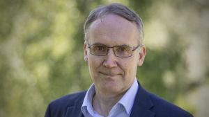 Närbild på man i blå kostym, ljusblå kragskjorta och glasögon. SOK:s verkställande direktör Taavi Heikkilä.