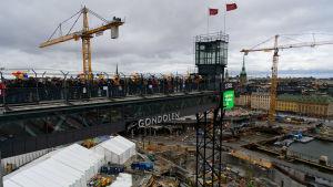 Folk på Katarina gångbro och Slussenbygget nedanför.