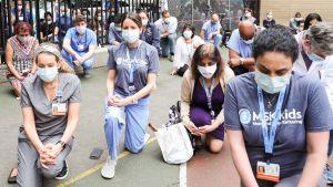 På bilden syns en stor samling sjukhusanställda som gått ner på knä för att visa sitt stöd för de antirasistiska demonstrationerna. Personerna står en bit ifrån varandra iklädda ansiktsskydd.