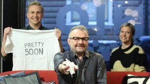 """Seppo Fränti sitter i Efter Nios soffa och håller upp toapappersrullen. I bakgrunden finns Sonja Kailassaari och Janne Grönroos, osm håller upp skjortan med texten """"Pretty Soon"""""""