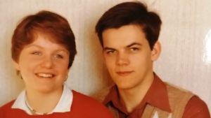 Ett gulnat fotografi av en kvinna och en man som ler mot kameran.
