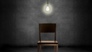 Trästol i ett mörkt rum med en glödlampa hängande ovanför