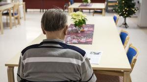 En äldre man sitter i rullstol vid ett bord på ett servicehem.