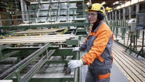 Processarbetare iklädd hjälm står produktionslinje för sågat virke.