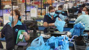 Kassapersonal i ett snabbköp i Miami, Florida använde både skyddsmasker och handskar på måndagen.