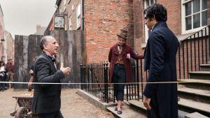 På bilden syns regissören Armando Iannucci (till vänster) ge instruktioner till skådespelarna Peter Capaldi och Dev Patel under inspelningarna av den nya David Copperfield-filmen. Skådespelarna är iklädda kläder tidtypiska för 1800-talet.