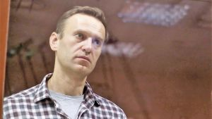 Den ryska oppositionsledaren Aleksej Navalnyj, bakom en glasruta, iklädd uppknäppt, rutig skjorta med t-skjorta under.