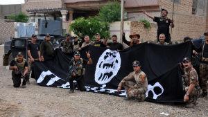 Irakiska specialstyrkor poserar med Islamiska statens flagga efter återerövringen av staden Heet i västra Irak 14.4.2016