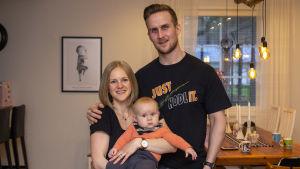 En kvinna och en man håller om varandra. Kvinnan har en bebis i famnen. De står i sitt vardagsrum.