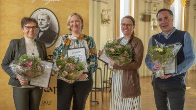 Fyra personer står på rad och håller i diplom och blommor medan de tittar in i kameran. Från vänster: Annica Törmä, Tiina Sjelvgren, Jenny Sylvin och Jens Berg.