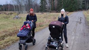 Sara och Erika står på en väg med sina barn i vagn.