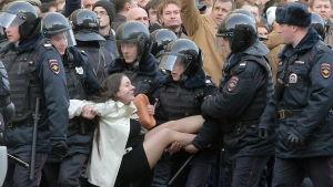 Rysk kravallpolis bär bort en demonstrant under protesten i Moskva 27.3.2017