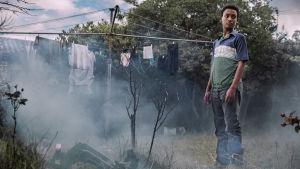 Nuori, n. 12-14-vuotias tummaihoinen poika seisoo kotinsa sumuisella takapihalla ruosteisen pyykkitelineen vieressä.