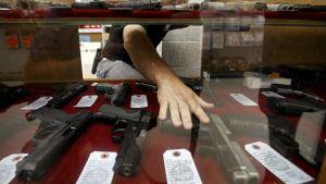 Man sträcker sig efter en pistol i en vapenaffär i Kansas