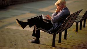 Pensionär sitter på en bänk