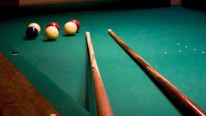 biljardbollar och -köer på ett bord