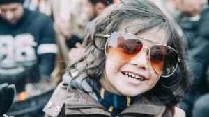 liten flicka med stora solglasögon