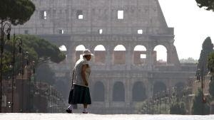 En kvinna korsar gatan intill Colosseum i Rom-