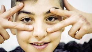 en mörkhårig pojke med stora vackra ögon kikar mellan fingrarna