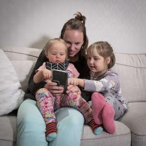 Äiti pitelee pientä lasta polvellaan. Äidin oikealla puolella on toinen vähän vanhempi lapsi, joka koskettaa älypuhelimen näyttöä.
