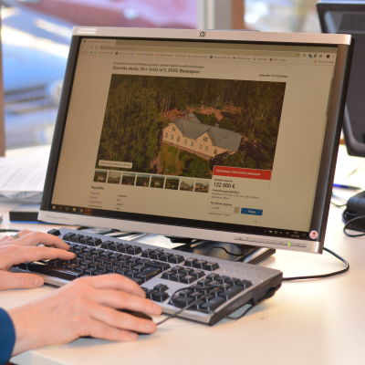 Datorskärm där det pågår nätauktion på ett stort ljusgult trähus.