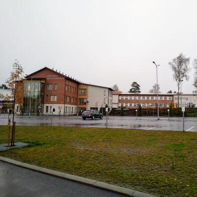 I bakgrunden syns en stor skola, framför finns en tom parkeringsplats med endast en bil.