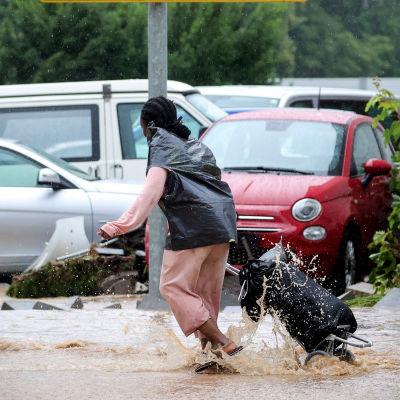 En kvinna med en väska på släp tar sig över en översvämmad parkeringsplats. Vattnet når till hennes anklar.