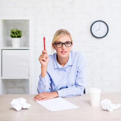 kvinna med glasögon skriver en lista och ser ivrig ut