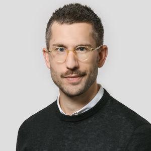 porträttbild av alexander rozental. han bär en mörk tröja och har glasögon med genomskinliga plastbågar i en gulaktig färgnyans.