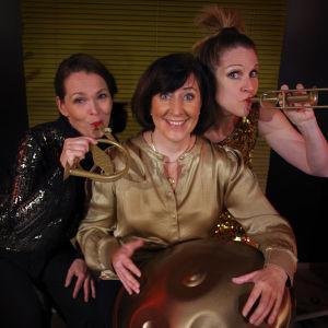 Tre kvinnor i festklänningar ler in i kameran. De håller upp små blåsinstrument i plast.